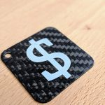 Keyring made of carbon fibre with a dollar symbol UV printed in white.